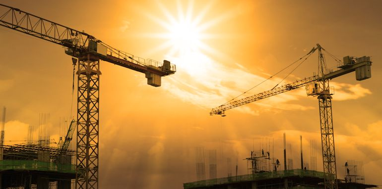 file of crane and building construction and sun set sky